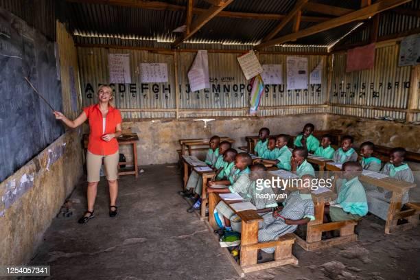 volunteer teaching in africa, school near masai mara game reserve in kenya - native african girls stock pictures, royalty-free photos & images