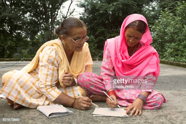 Volunteer teaching old lady to write adult literacy program socio-economic initiative started by NGO Chinmaya Organization
