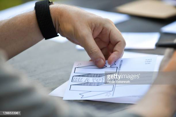Volunteer Thomas Hollier fills out postcards encouraging voters to mail-in ballots during the 2020 elections on August 15, 2020 in Los Angeles,...