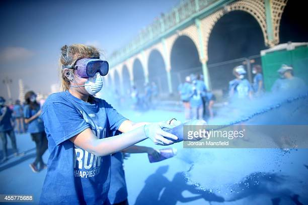 A volunteer throws powder on the runners during the Color Run presented by Dulux known as the happiest 5km on the planet on September 20 2014 in...