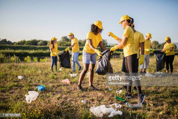volunteer together pick up trash in the park - social issues stock pictures, royalty-free photos & images