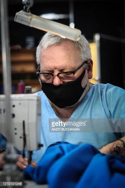 Volunteer Tony McGlynn works to produce free scrubs for the National Health Service at Tailor Thomas Rae's workshop in Glasgow on April 16 2020...