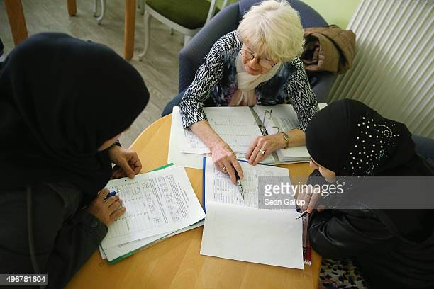 Volunteer tutor Luise Braeuer instructs asylumapplicants Taghreed Hamud from Syria and Hadijat from Chechnya in a Germanlanguage class at the Gierso...