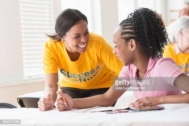 Volunteer tutoring student in classroom