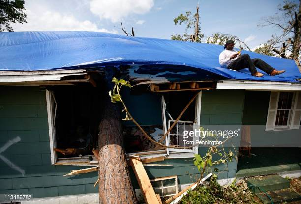 Volunteer Tyrone Duncan secures a blue tarp to a damaged house on May 2 2011 in Tuscaloosa Alabama Alabama the hardesthit of six states is reported...