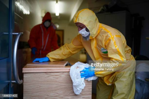 Volunteer undertaker Farak Malik disinfects a coffin after performing Ghusl, the sacred Islamic ritual of bathing the deceased, on a Covid-19...