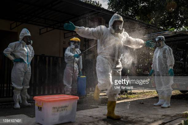 Volunteer undertakers is sprayed with disinfectant as preparing before they recovering the body of a woman suspected to have died from COVID-19 while...