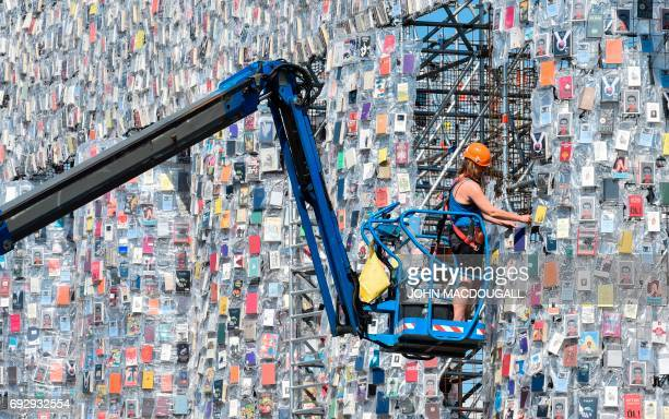 A volunteer uses a mobile lift to hang books on the Parthenon of Books by Argentinian artist Marta Minujin at the Documenta 14 art exhibition in...