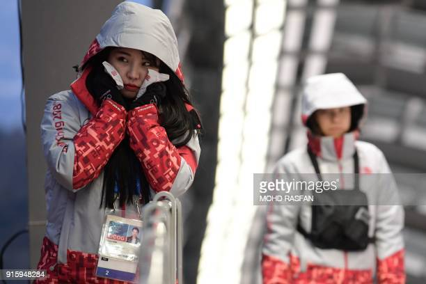 A volunteer uses hand warmers at the Olympic Sliding Centre ahead of the Pyeongchang 2018 Winter Olympic Games in Pyeongchang on February 8 2018 /...