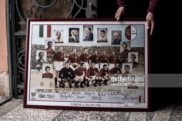 Volunteer Vito Mazzilli holds the poster of the team of Grande Torino in the Museum of Grande Torino and Granata's legend in Grugliasco near Turin on...