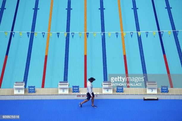 TOPSHOT A volunteer walks along the swimming pool of the Optus Aquatic Centre ahead of the 2018 Gold Coast Commonwealth Games on March 30 2018 / AFP...