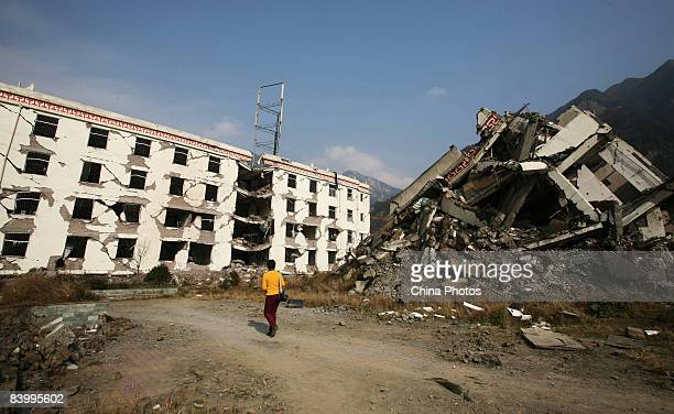 A volunteer walks past debris left by the May 12 Sichuan Earthquake at Xuankou Township's middle school on December 10 2008 in Wenchuan County of...