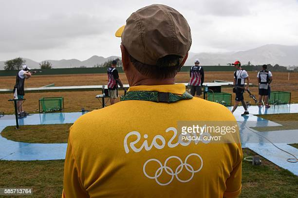 Volunteer watches athletes training for the double trap shooting event at the Olympic Shooting Centre in Rio de Janeiro on August 3 ahead of the Rio...