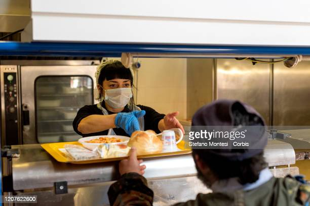 Volunteer wearing a face mask serves the meal to a homeless at the canteen of Caritas Colle Oppio, the canteen serves 400 meals a day, during the...