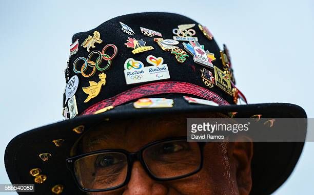 A volunteer wearing a hat with Olympic pin badges looks on at the Athletes village on August 3 2016 in Rio de Janeiro Brazil
