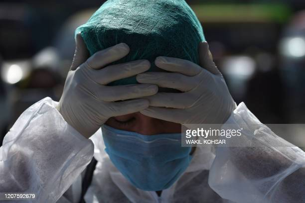 Volunteer wearing a hazmat suit and a facemask prepares before the start of a preventive campaign against the spread of the COVID-19 coronavirus, in...