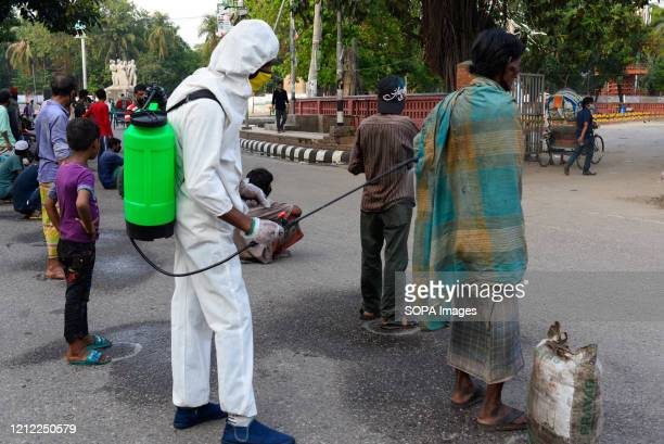 Volunteer wearing a protective suit disinfects a homeless man as a preventive measure during the Coronavirus crisis. Volunteers from Dhaka University...