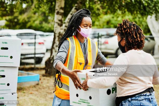 volunteer wearing protective face mask giving away csa box at community center - volunteer stock pictures, royalty-free photos & images