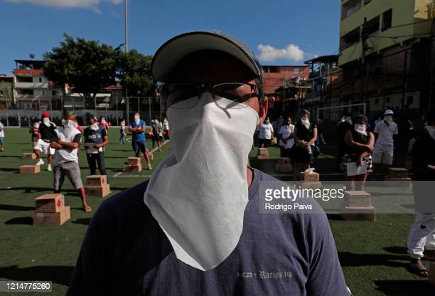 A volunteer wears a protective mask during training session before delivering free food to residents of Paraisópolis favela on March 24 2020 in Sao...
