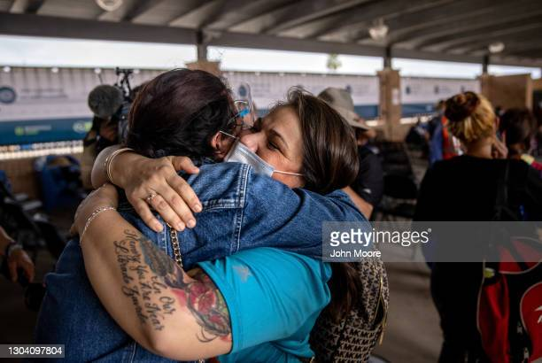 Volunteer welcomes a group of at least 25 immigrant asylum seekers who were officially allowed to cross from a migrant camp in Mexico into the United...