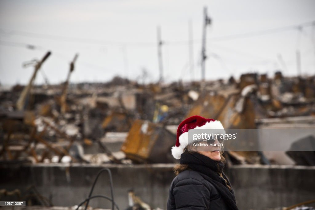 A volunteer who would only identify herself as 'Nancy' steps back after helping decorate a Christmas Tree December 25, 2012 in the Breezy Point neighborhood of the Queens borough of New York City. Residents are still struggling to recover from a massive fire that destroyed over 100 homes during Superstorm Sandy.