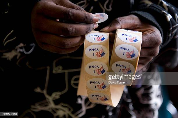Volunteer William Clark hands out 'I Voted' stickers at New Covenant ARP Church Precint 28 in Charlotte NC on election day Nov 4 2008 Voting is...