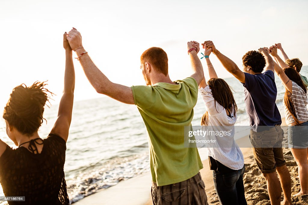 volunteer with arm raised at sunset : Stock Photo