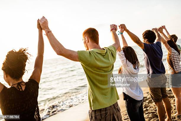 volunteer with arm raised at sunset - global village stock pictures, royalty-free photos & images