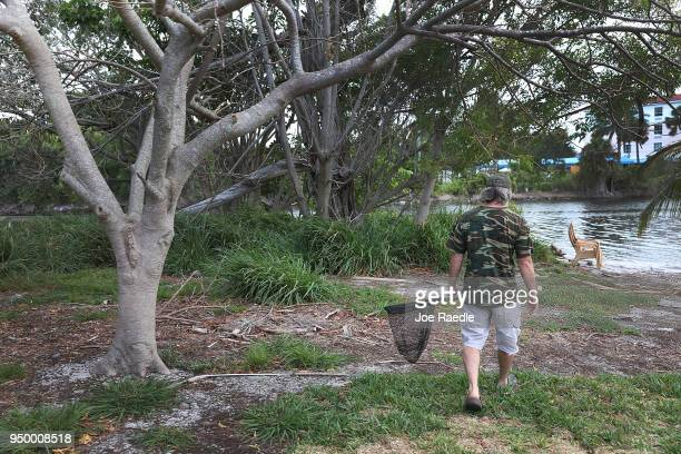 A volunteer with East Coast Rabbit Rescue prepares to use a net to capture rabbits near Pioneer Canal Park on April 22 2018 in Boynton Beach Florida...