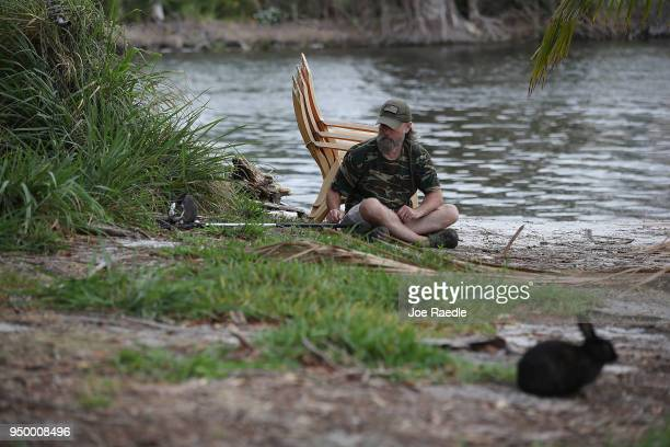 A volunteer with East Coast Rabbit Rescue uses a net to capture a rabbit near Pioneer Canal Park on April 22 2018 in Boynton Beach Florida The...