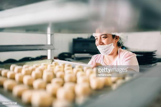 volunteer with intelectual disability working at bakery workshop - discapacidad intelectual fotografías e imágenes de stock