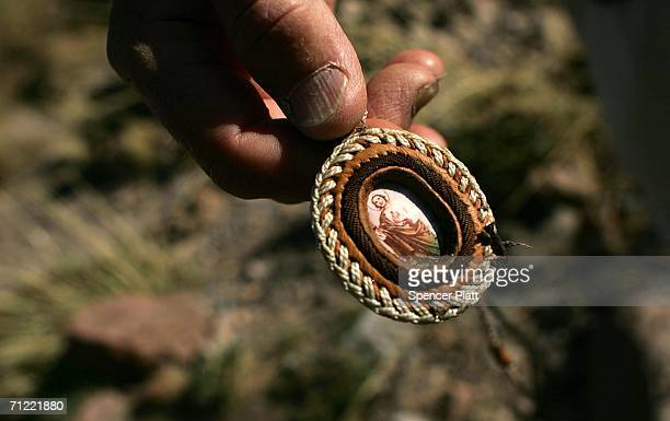 A volunteer with the humanitarian group No More Deaths displays a religious pendant picked up from the ground on a trail used by migrants illegally...