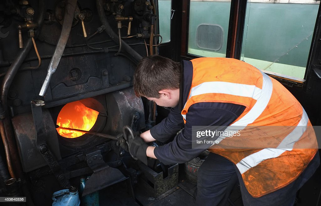 A volunteer with the North Yorks Moors Railway stokes the fire of a locomotive at Grosmont train engine sheds in preparation for the ceremony to mark a second platform opening at Whitby train station on August 15, 2014 in Whitby, England. The second platform will provide passengers with more options for travel to the Yorkshire seaside town on the North Yorks Moors Railway and was the first time in half a century two steam locomotives were side by side at the station.