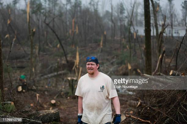 A volunteer with the United Aid Foundation works in the rain to clear fallen trees and debris in the aftermath of an EF4 tornado on March 11 2019 in...