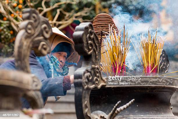 volunteer woman organizing incense bin - merten snijders stock-fotos und bilder