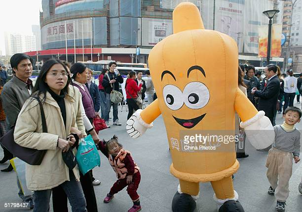 Volunteer worker dressed as a giant condom plays with passers-by during an event organized by the local government to promote AIDS prevention on...