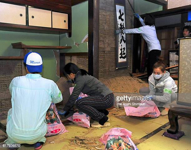 Volunteer workers clear fallen clay wall at a dameged building two days after magnitude 6.6 earthquake hit the area on October 23, 2016 in Hokuei,...