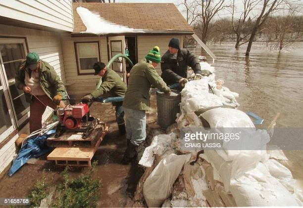 Volunteer workers in Granite Fall Minnesota use a water pump to keep flood waters from getting into a home 08 April start a pump to pump out a...