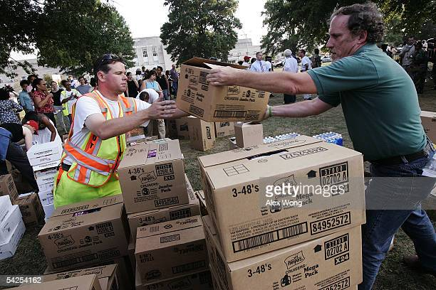 Volunteer workers John Ingersoll and Eric Hauser help to distribute supplies to the buses that will be sent to New Orleans to evacuate hurricane...