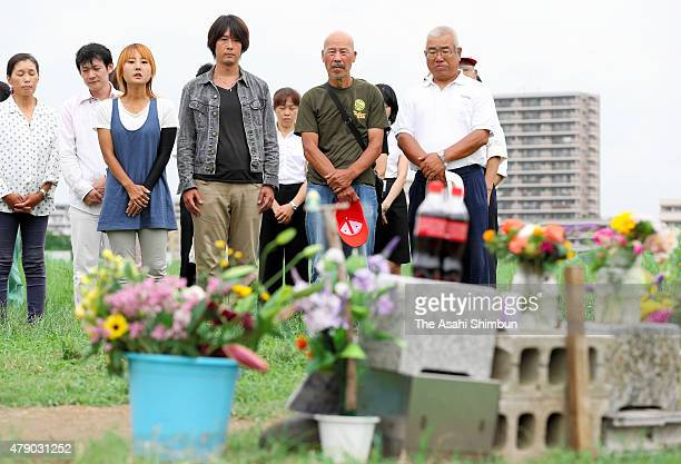 Volunteer workers observe a minute of silence before removing a makeshift altar for killed 13yearold Ryota Uemura at Tamagawa River on June 30 2015...