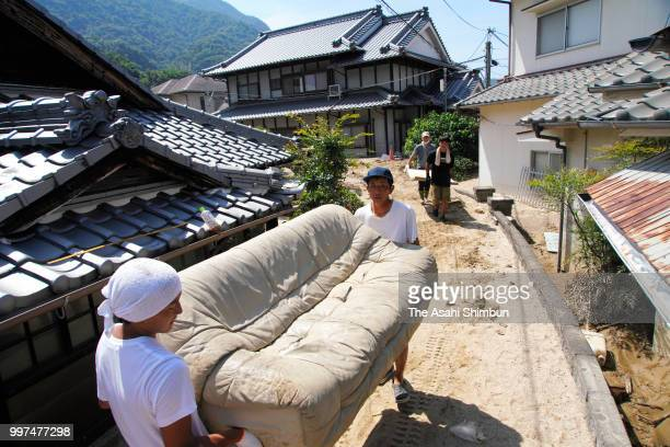 Volunteer workers remove a damaged sofa on July 13 2018 in Kure Hiroshima Japan The death toll from the torrential rain in western Japan due to...