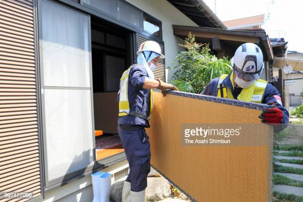 Volunteer workers take out a damaged tatami mat on July 13 2018 in Kurume Fukuoka Japan The death toll from the torrential rain in western Japan due...