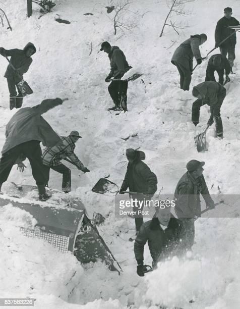 Volunteer workmen are shown digging near a smashed highway dept truck in hopes of finding John Hermann a Salt Lake City cameraman and Wayne Whitlock...