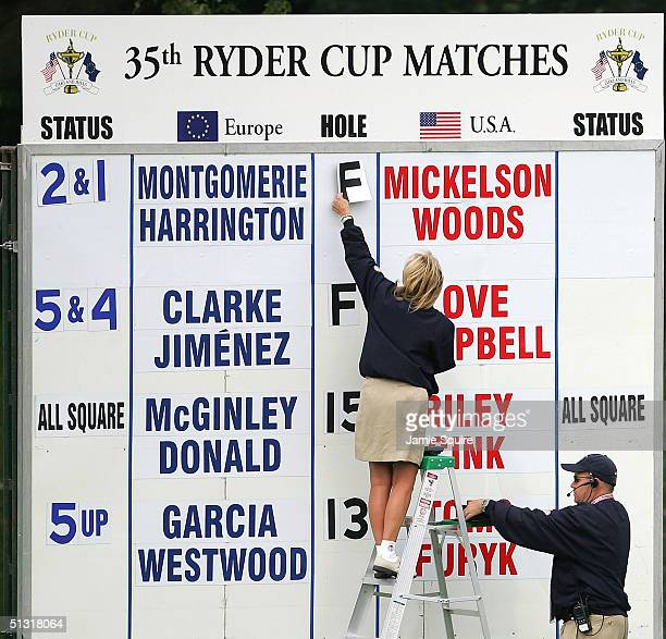 Volunteer works a scoreboard near the end of the morning four-ball match with Tiger Woods and Phil Mickelson at the 35th Ryder Cup Matches at the...