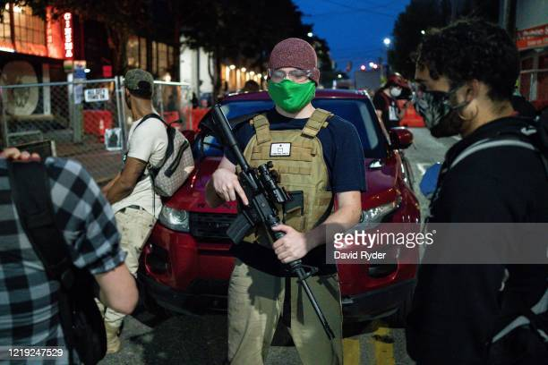A volunteer works security at an entrance to the socalled Capitol Hill Autonomous Zone on June 10 2020 in Seattle Washington The zone includes the...