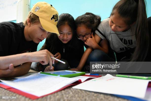 Volunteer youth counselor Connor Jones left helps Sarah second from left Sher Deh 11 and Yeh Doh right work on making their Write Our Word ebook...