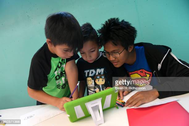 Volunteer youth counselor Ler Moo right helps campers Pedro left and Mateo middle work on making a Write Our Word ebook during summer day camp at the...