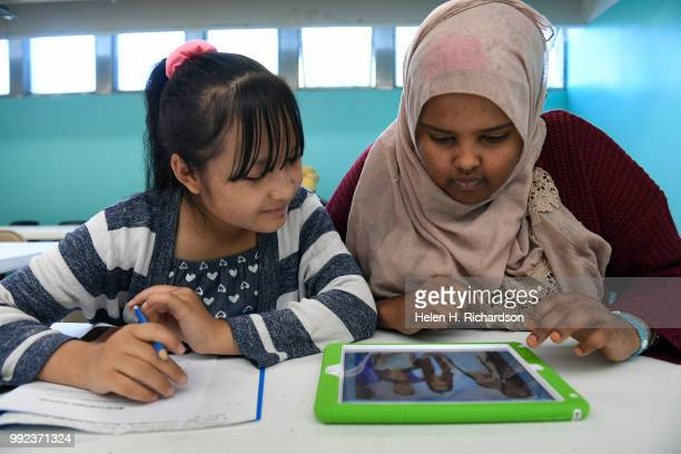 Volunteer youth mentor and counselor Farhiya Yussuf right helps Eh Ku left work on making a Write Our Word ebook during summer day camp at the...