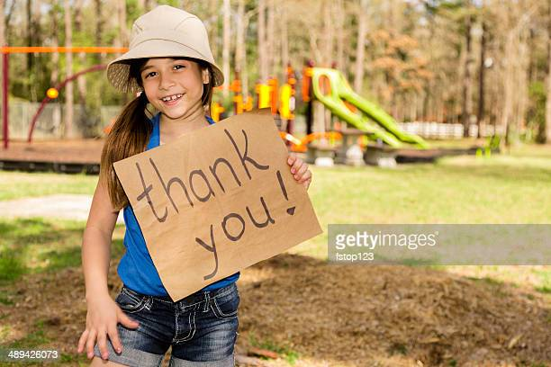 """volunteerism: cute little girl holds """"thank you"""" sign. local park. - thank you phrase stock pictures, royalty-free photos & images"""