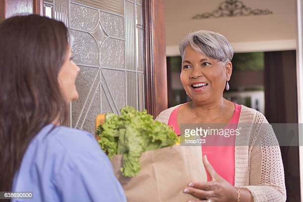 volunteerism: senior adult woman receives groceries at home. - meals on wheels stock pictures, royalty-free photos & images